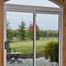 interior recreation room view of two panel white vinyl patio door with knotty pine surround