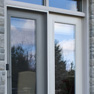 exterior deck view of grey stained vinyl terrace door and white vinyl fixed door wth transoms
