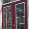 exterior deck view of red stained vinyl two panel terrace door and transom featuring grills