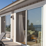 exterior deck view of three white vinyl patio doors on long patio deck