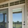 exterior patio view of beige vinyl terrace door with grey and beige fixed doors with transom featuring grills