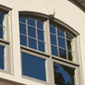 exterior view of four panel shaped top wicker stained vinyl slider windows with matching side windows featuring grills