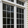 exterior patio view of white vinyl fixed windows with transom featuring grills