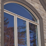 exterior view of three pane ivory stained casement window with shaped transom and pebble stained trim