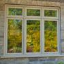exterior garden view of set of three sandstone stained fixed and casement windows and transom